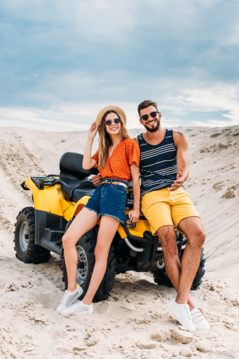 young couple leaning back on an atv in the desert