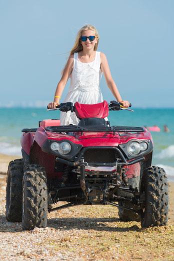 girl in sunglasses riding an atv on a beach