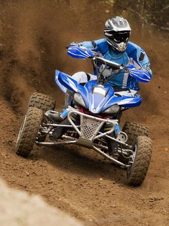 quad driver racing on a dirt trail